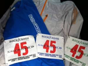 Pre-race shirt, three race bibs, and a finisher's jacket.