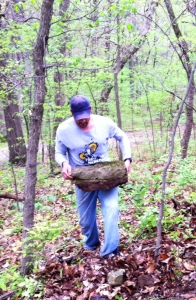 Wayne Garner hauls a rock to the rock garden in a new section of trail at Wyandotte County Lake Park.